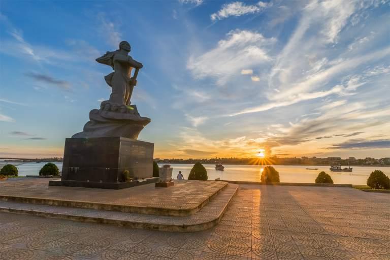 Tượng đài mẹ Suốt in bóng xuống dòng sông lịch sử