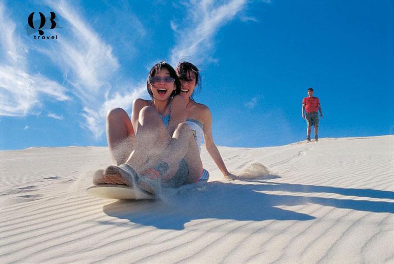 Du khách trải nghiệm trò chơi trượt cát tại bãi biển Quang Phú