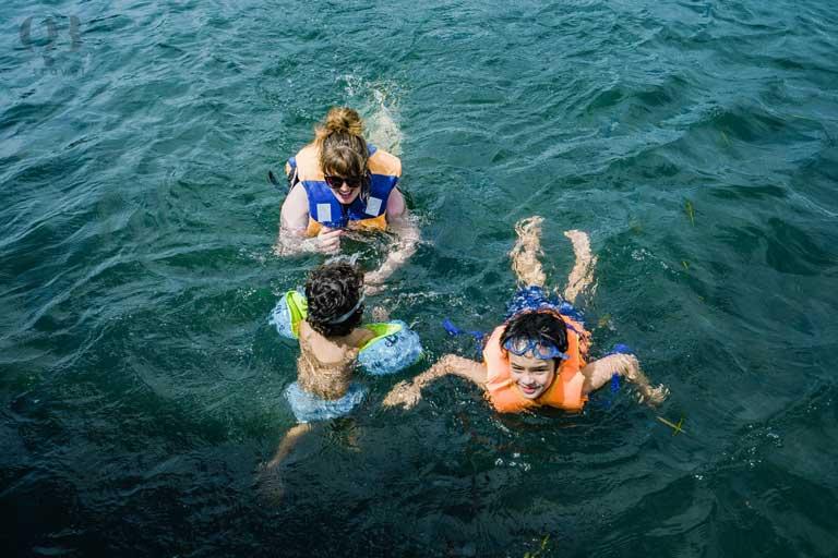 Các bạn nhỏ cùng mẹ bơi lội ở bãi đá cạn
